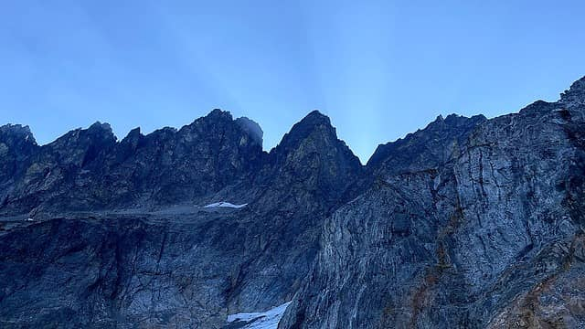 Sun rays streaming off the jagged ridge of Seven Fingered Jack.