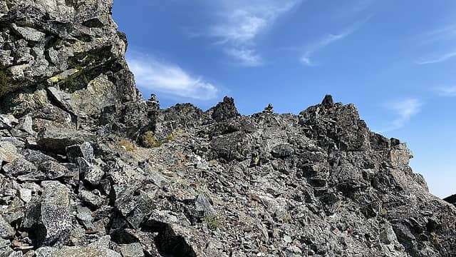 Approaching the summit block – the route traverses to the right of the large formation on the right and turns back on itself to the final summit block requiring about 200 feet of scrambling to attain the summit.
